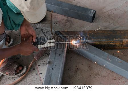 Man Weld A Metal With A Welding Machine.