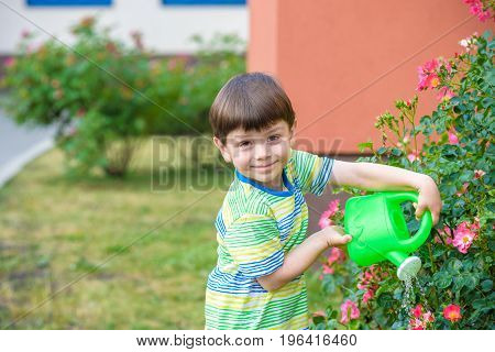 Cute Little Boy Watering Plants With Watering Can In The Garden.