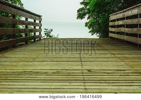 A wooden bridge leading toward a hazy lake in the background.