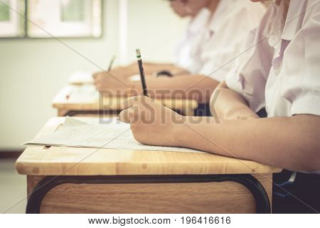 Asian girls students writing test exams on paper for Admissions in high school with uniform student in row seat School classroom of Thailand taking exam background and education concept vintage tone