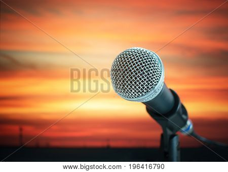 close-up of microphone on stand in live concert or conference room on sunset colorful light background