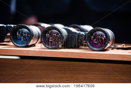 Group Of Journalists Reflected In Glasses Of Binocular