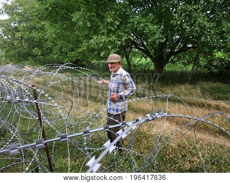 Old Man On Local Stand Near Barbed Wire
