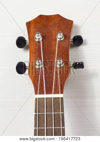 Headstock of Ukulele Hawaiian Guitar onwhite wooden background