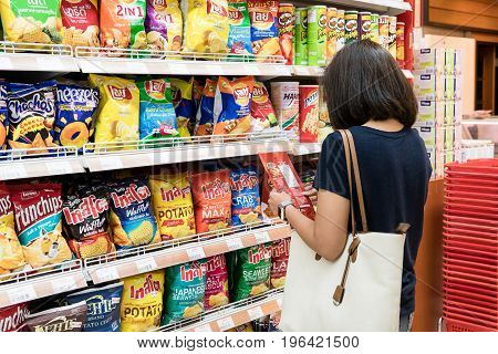 Foodland Superstore, Bangkok, Thailand - May 20, 2017: Middle aged women is buying snacks. By choosing from the nutrition and calories.