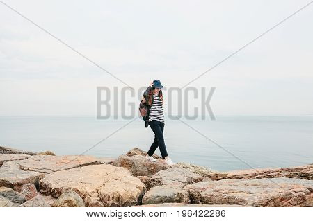 A traveler in a hat with a backpack walks next to the sea. Travel, tourism.