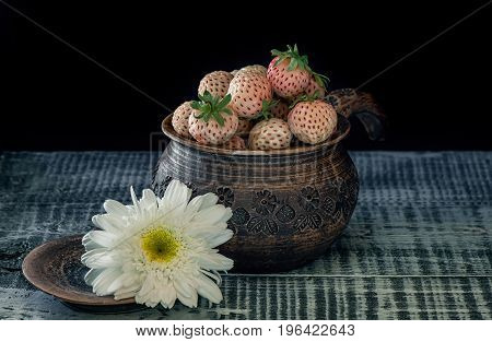 Ripe fresh white strawberries in a clay pot in a rustic style on a black background. Art. A horizontal frame.