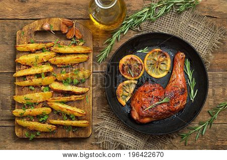 Roasted chicken leg and potato wedges on wooden table top view
