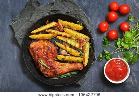 Fried chicken leg and potato wedges in frying pan top view