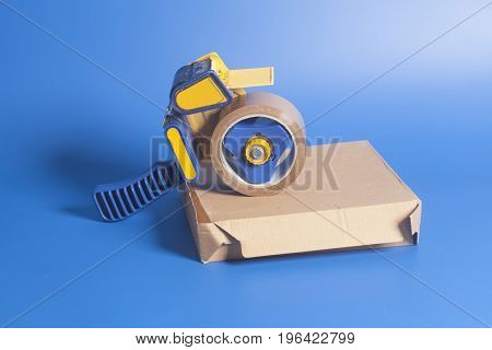Industrial Tape Dispenser On A Cardboard Box