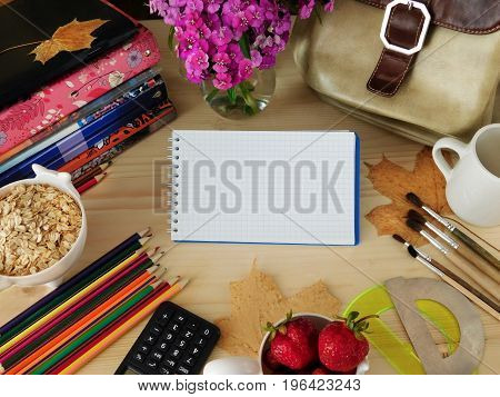 School supplies and breakfast ingredients on a wooden table. Notebook with a blank page in the middle