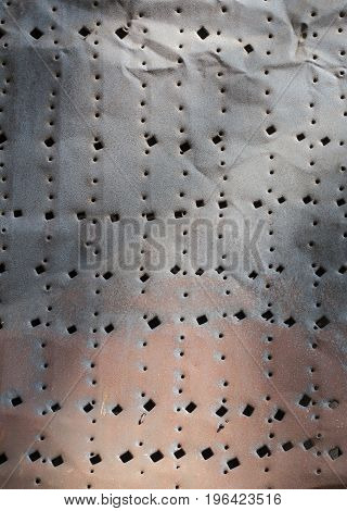 Grunge rust texture of half painted metal sheet with random holes in circles and squares shapes