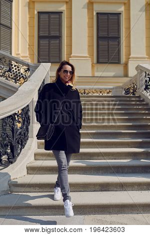 Trendy woman wearing sunglasses walking down an exterior flight of stone stairs looking away to the right of the frame with a happy smile