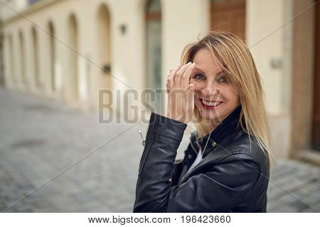 Attractive blond woman standing outdoors in a courtyard flicking her long blond hair off her face with her hand as she smiles at the camera