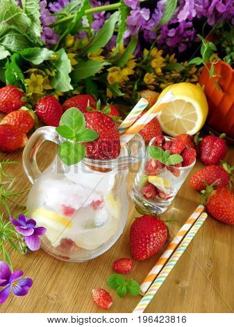 Glass jug is full of ice cubes, berries, lemon and mint decorated with strawberry and multicoloured straws. Flowers in the background