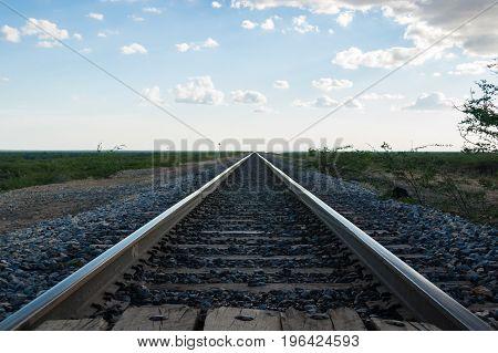 Railroad tracks converging at the horizon during sunset