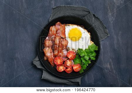 Fried egg with bacon tomatoes and parsley in frying pan on dark background top view