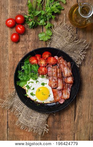 Fried egg with bacon tomatoes and parsley in frying pantop view