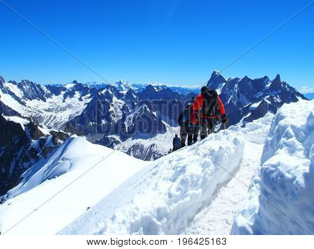Two alpinists and mountaineer climber on AIGUILLE DU MIDI, CHAMONIX MONT BLANC french ALPS, top alpine mountains range landscape, FRANCE with clear blue sky in 2016 warm sunny summer day Europe on July