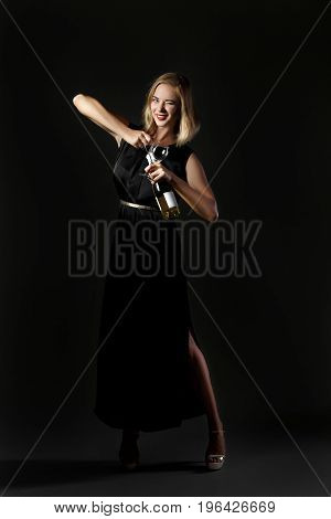 Beautiful blonde woman holding a white wine bottle on a black background. Party and holiday