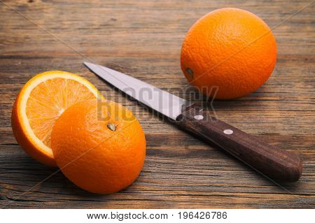 Juicy oranges on a wooden background. Cutted orange on the table on the table.