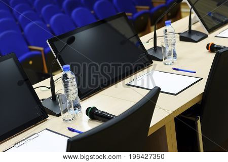 Conference hall for business meeting, table with microphones, monitors, bottles with water, glasses, papers, pens and chairs, blue seats in row on blurred background, selective focus