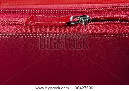 Red leather bag with zipper and stitches, detail, woman accessories, fashion industry, macro shot, selective focus