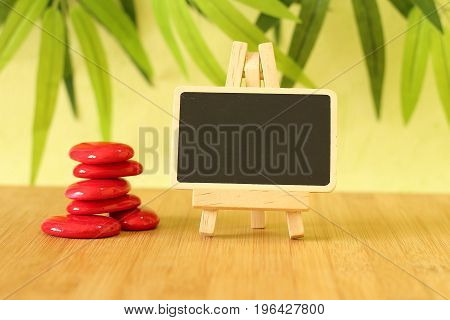 Small empty slate in width to write a message that is posed on an easel with  zen lifestyle red stones all on wooden floor and green foliage background