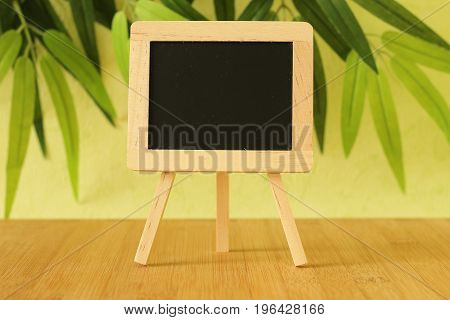 Small empty blackboard to write a message posed on an easel on a wooden floor with a green foliage background