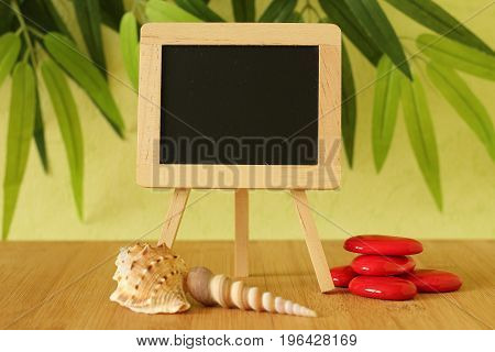 Small empty blackboard to write a message posed on an easel on a wooden floor with red pebble and beach shells on a green foliage background