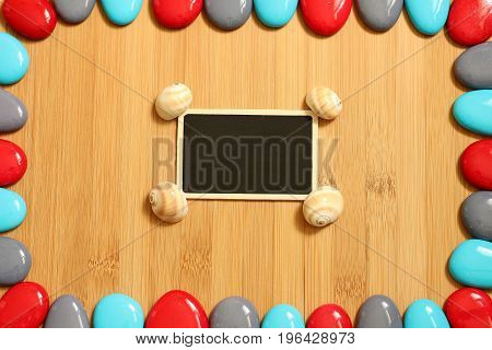 Small red gray and blue pebbles arranged all around a brown bamboo wood floor with in the center an empty slate to write a message and snail shells