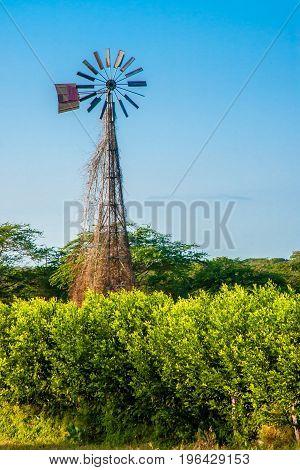 Old broken windmill at sunset under blue sky