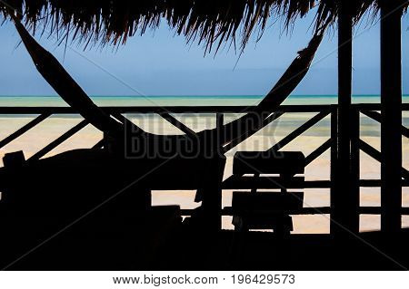 Silhouette of a hammock at a cottage next to the sea