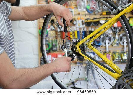 Young man working in bicycle repair shop, closeup