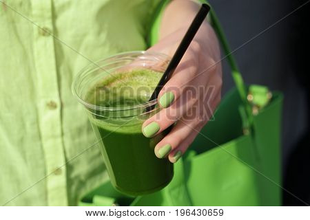 Woman holding cup of green smoothie, closeup