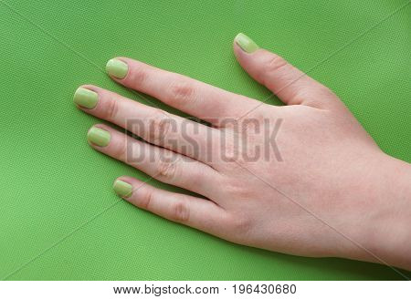 Beautiful female hand with green manicure on color background