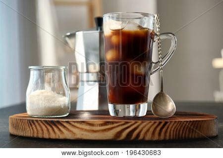 Glass cup with cold brew coffee and sugar bowl on cutting board