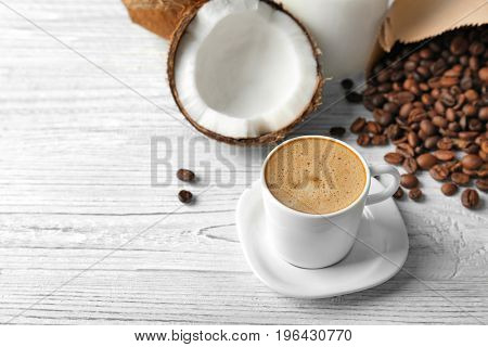 Cup of tasty coconut coffee, beans and nut on wooden table