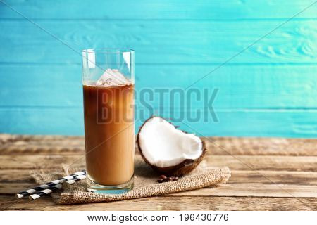 Glass of cold tasty coconut coffee on table