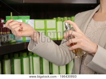 Young woman testing perfume on skin in store