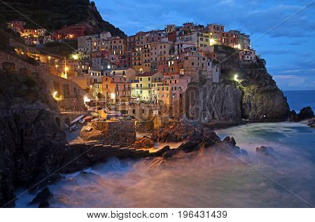 dusk on the hillside town of Manarola, Cinque Terre, Italy.  Time exposure of waves crashing on rocks.