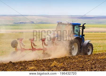 side view of blue tractor ploughing a field with trail of dust behind it