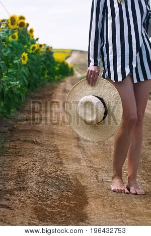 vertical closeup of bare feet Caucasian woman with stripe shirt holding a white wicker hat next to a sunflower field