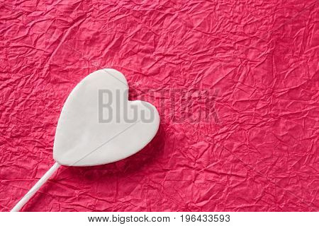 Tasty candy in shape of heart on color crumpled paper