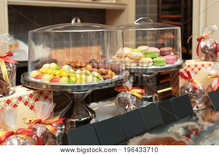 Stands with tasty sweets on table in shop