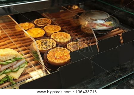 Fridge with bakery products in shop, closeup