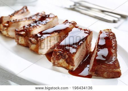 Delicious pork ribs with soy sauce on plate, closeup
