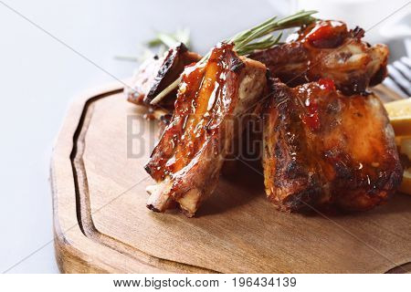 Delicious pork ribs with rosemary on wooden board, closeup