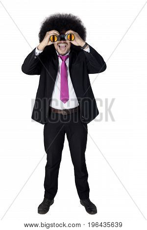 Surprised Afro businessman looking through a binoculars isolated on white background