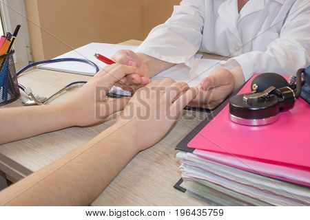 Female Doctor and patient are discussing something just hands at the table. Hand of doctor reassuring her female patient